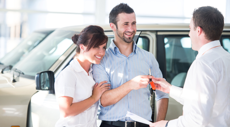 Happy couple getting car keys from a car seller